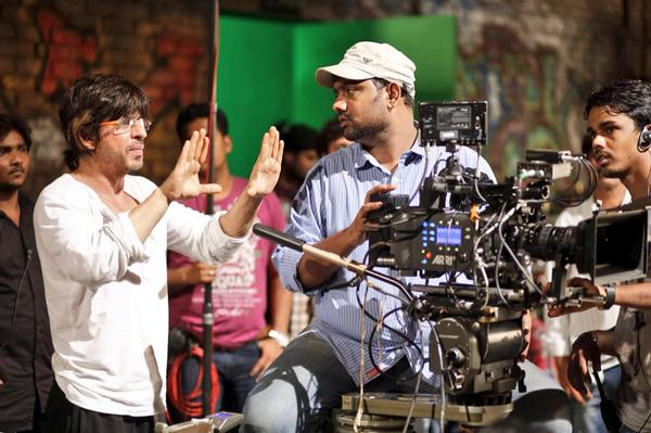 Happy New Year Charlie is animatedly discussing a shot with DOP Manush Nandan on the sets of HNY .